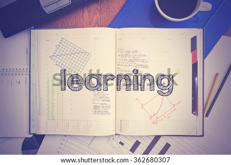Notebook with text inside associated with the education - Learning . On table are coffee, laptop and some sheet of papers with charts and diagrams - stock photo