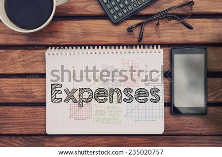 Notebook with text inside Expenses on table with coffee, mobile phone and glasses.  - stock photo