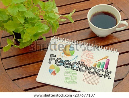 Notebook with text inside Feedback on table with coffee and plant. - stock photo