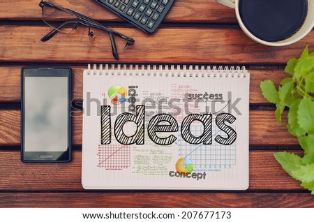 Notebook with text inside Ideas on table with coffee, mobile phone and glasses.  - stock photo