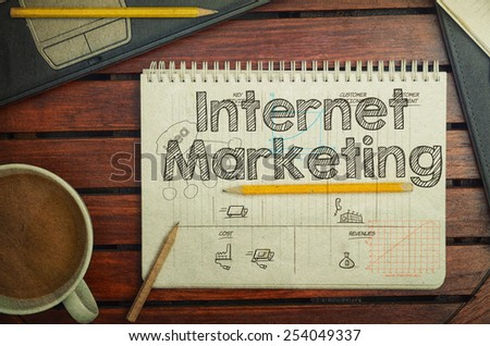 Notebook with text inside Internet Marketing on table with coffee, notebook and pencils, retro filter - stock photo