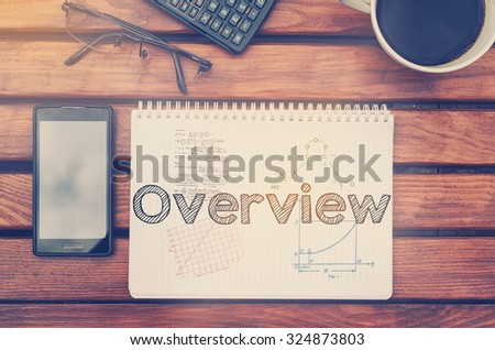 Notebook with text inside Overview on table with coffee, mobile phone and glasses.  - stock photo