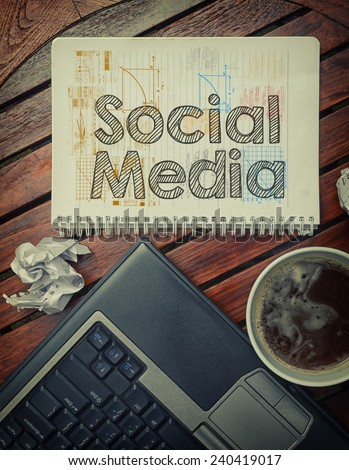 Notebook with text inside Social Media on table with coffee, laptop pc and crumpled sheets - stock photo