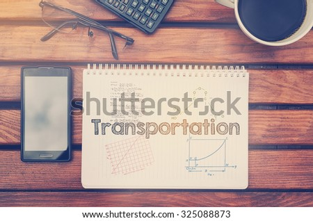 Notebook with text inside Transportation on table with coffee, mobile phone and glasses.  - stock photo