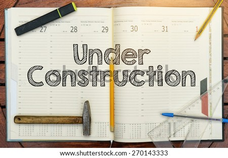 notebook with the note in the center Under Construction - stock photo