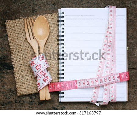 notebook Wrapped with a tape measure with wooden fork and spoon .notebook with space. lose weight concept. - stock photo