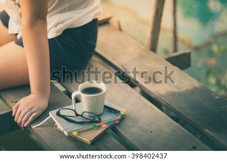 Notebooks, pen, glasses, and coffee cup are putting down on the wood bridge while young woman sitting beside them in morning time on weekend with instagram vintage filter effect - stock photo
