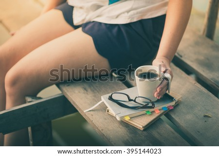 Notebooks, pen, glasses, and coffee cup are putting down on the wood waterside with young woman left hand holding coffee cup in morning time on weekend with vintage filter effect - stock photo