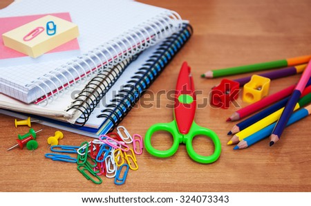 notebooks with school supplies on a wooden background - stock photo