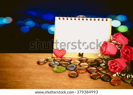 notepad and bunch of roses with blur bokeh light in city background - stock photo