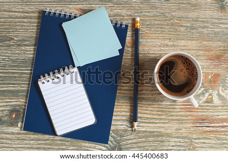Notepad and cup of coffee on old wooden table, top view. Space for your text - stock photo
