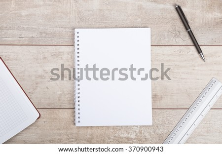 Notepad and pen on wooden table - stock photo