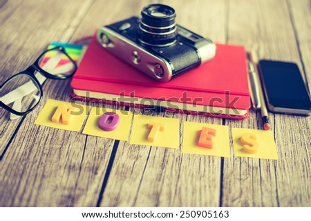 Notepad, camera and smartphone - stock photo