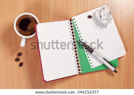 Notepad, crumpled paper, pen and coffee cup on desk, top view - stock photo