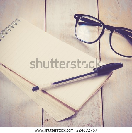 notepad,glasses and ink pen on the wooden, retro filter effect - stock photo