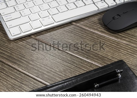 Notepad, keyboard, mouse and cellphone on wood table - stock photo