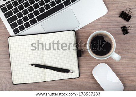 Notepad, laptop and coffee cup on wood table. View from above - stock photo
