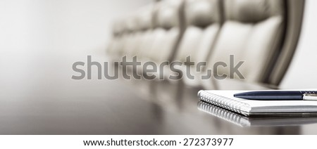 Notepad on table in empty conference room with copy space - stock photo