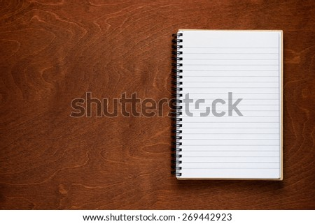 Notepad on wooden background - stock photo