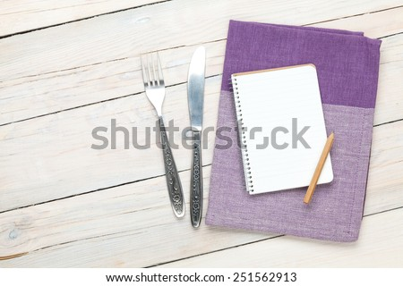 Notepad over kitchen towel and silverware on wooden table with copy space - stock photo
