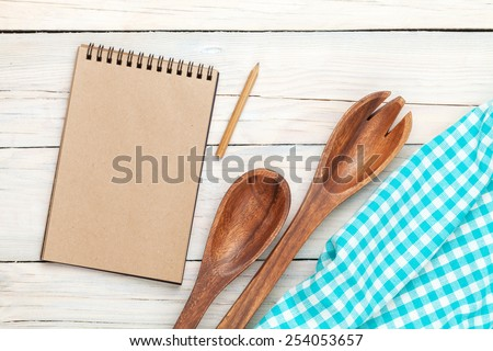 Notepad over kitchen towel and utensils on wooden table with copy space - stock photo