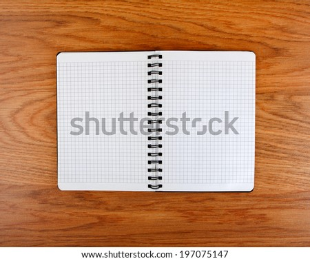 Notepad with a spiral binding and checkered sheets on a wooden background - stock photo