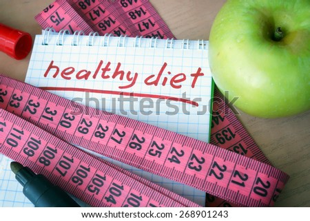 Notepad with healthy diet  and measuring tape. - stock photo
