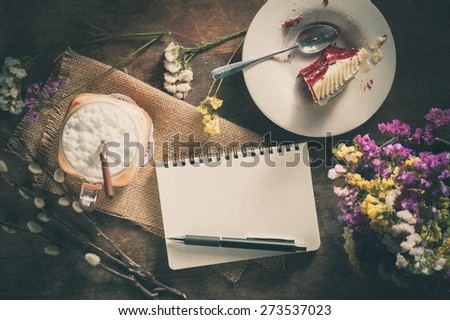 Notepad with pen, a glass of Thai tea and bits of red velvet cake on rustic wood background with film filter effect - stock photo