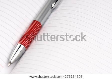 Notepad with red ball pen on a white background. - stock photo