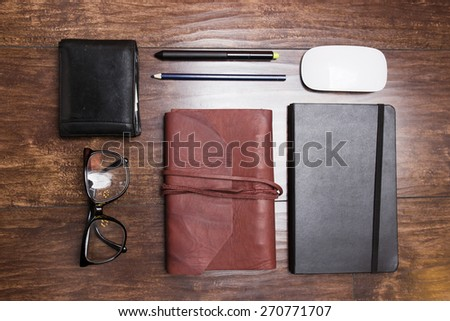 Notepads in leather cover with pencils and eyeglasses on wooden background - stock photo
