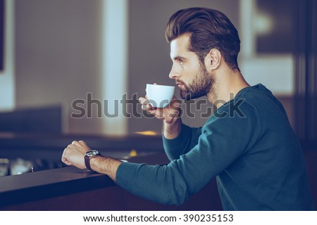 Nothing better then cup of fresh espresso. Side view of handsome young man drinking coffee while sitting at bar counter - stock photo
