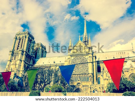 Notre Dame Cathedral in Paris and colorful flags at foreground. Selective focus on the Notre Dame Cathedral. Retro aged photo. - stock photo
