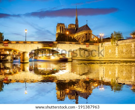 Notre Dame cathedral with boat during evening in Paris, France - stock photo