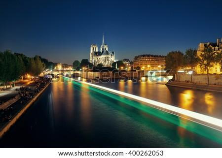 Notre Dame de Paris at dusk over River Seine with boat light trail as the famous city landmark. - stock photo