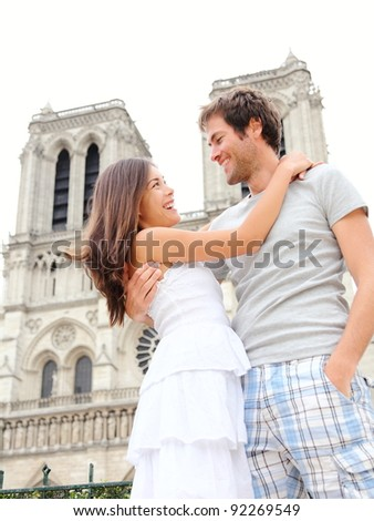 Notre Dame de Paris. Happy young couple in front of Notre Dame Cathedral in Paris, France. Asian woman and Caucasian man. - stock photo