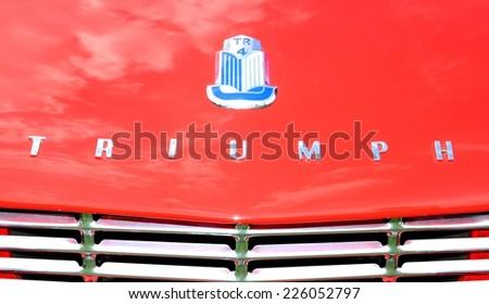 NOTTINGHAM, UK - JUNE 1, 2014: Close up of logo of a vintage Triumph car for sale in Nottingham, England. - stock photo