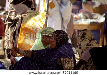 NOUAKCHOTT, MAURITANIA - JAN 5: Local woman sells her staff at the market on January 5, 2006 in Nouakchott, Mauritania. The city market is an interesting place to visit. - stock photo