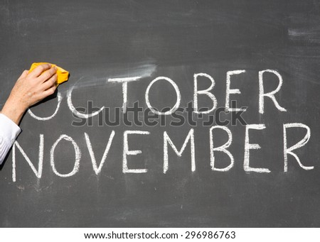 November is coming concept - inscription October and November on a school blackboard, with the words October being erased by the teacher. - stock photo