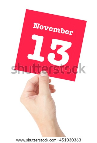 November 13 written on a card held by a hand - stock photo