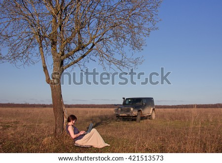 Novgorod oblast, Russia, April 16, 2016: girl working on the computer in the background of the Jeep Wrangler, Russia. Wrangler is a compact four wheel drive off road and sport utility vehicle - stock photo