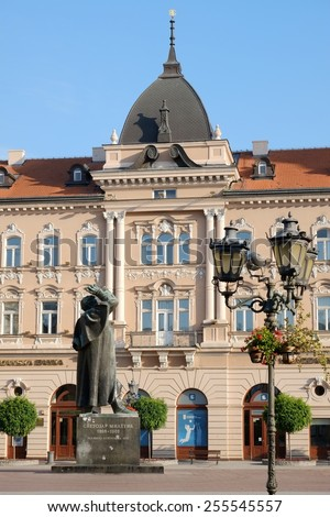 NOVI SAD, SERBIA - AUGUST 03: the bronze statue of Svetozar Miletic and neoclassical and baroque renaissance architecture in the Liberty Square of Novi Sad. Shot in 2014  - stock photo
