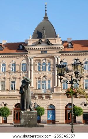 NOVI SAD, SERBIA - AUGUST 03: the bronze statue of Svetozar Miletic and neoclassical and baroque renaissance architecture in the Liberty Square of Novi Sad. Shot in 2014  - stock photo