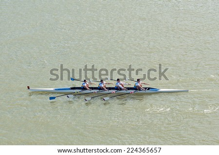 NOVI SAD, SERBIA - OCTOBER 18, 2014: Four men rowing on Danube River in Novi Sad on traditional remote regatta competition. - stock photo