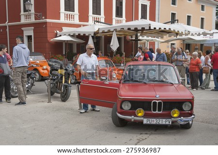 NOVIGRAD, CROATIA - SEPTEMBER 13, 2014: Unrecognizable people watch the parade of vintage cars on 5th International Old Timer Car Rally. The event organized by old timer club Eppur si muove from Umag. - stock photo