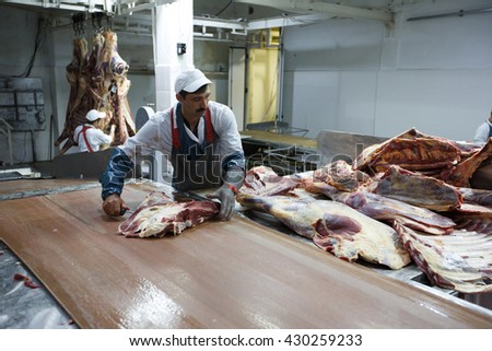 NOVOSIBIRSK/RUSSIA - 07.04.2011:Butchers chopping meat with cleaver, cut up carcasses of beef in Novosibirsk, Russia - stock photo