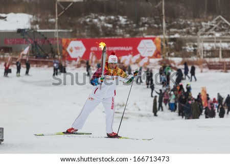 Novosibirsk, Russia - December 7, 2013 :Man climb on skis with the Olympic torch for the Olympic torch relay in Novosibirsk - stock photo