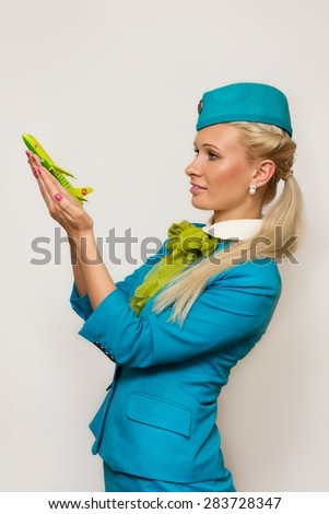 NOVOSIBIRSK, RUSSIA - JUNE 26, 2014: S7 Crew member (flight attendant) Holding Airplane In Hand. S7 is the founding airline of world's 3nd largest airline alliance - Oneworld. - stock photo
