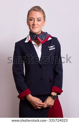 NOVOSIBIRSK, RUSSIA - NOVEMBER 02, 2015: Transaero Crew member (flight attendant) Dressed In Uniform On Gray Background. Transaero - largest private Russian airline has terminated operations Oct 2015 - stock photo