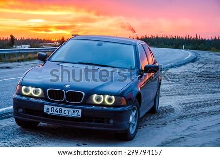 NOVYY URENGOY, RUSSIA - JULY 25, 2015: Business class sedan BMW E39 520i at the background of the sunset. - stock photo