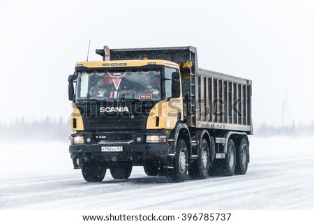 NOVYY URENGOY, RUSSIA - MARCH 20, 2016: Dump truck Scania P440 at the interurban freeway during a heavy northern blizzard. - stock photo